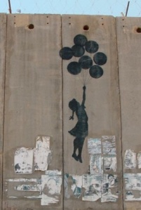 graffiti of a girlchild holding on to a bunch of balloons, which are carrying her over the wall the graffiti is painted on