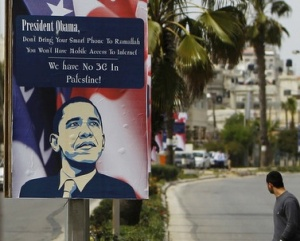 A Palestinian man walks near placards designed by an activist depicting U.S. President Obama, ahead of his visit to the region, in Ramallah
