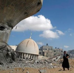 Palestinian women walk by mosque and water tower Israeli air strikes and shelling Khuzaa, east of Khan Younis, in southern Gaza Strip. August 3, 2014.  AFP