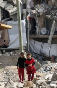 Palestinian girls walk past buildings in Gaza Thomas Coex AFP Getty
