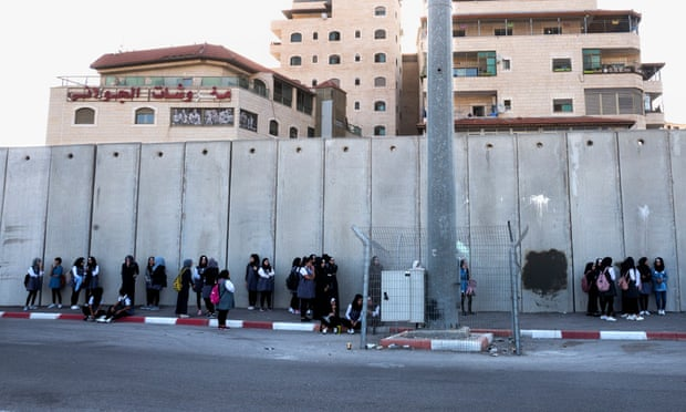 Image: Palestinian schoolgirls wait for buses in the shadow of the Israeli wall, inside the East Jerusalem Shua'fat refugee camp. Photograph: Jim Hollander/EPA